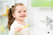 Smiling child girl brushing teeth in bathroom