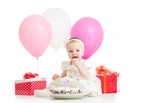 Smiling baby girl eating cake on first birthday