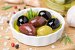 close-up of a bowl with different olives in olive oil and spices