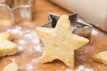 Christmas cookies in the shape of stars on a wooden board