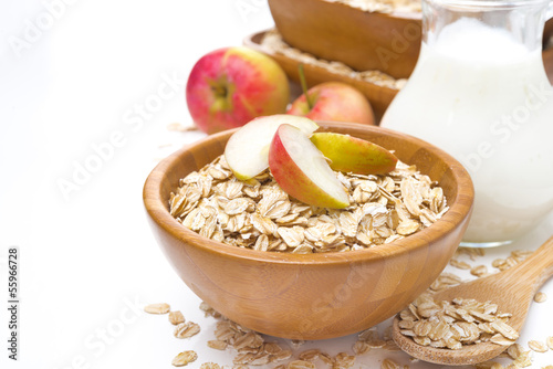 healthy breakfast - oat flakes with apples in a bowl and milk - 55966728