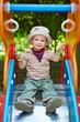 Junge sitzt auf der Rutsche auf dem Spielplatz