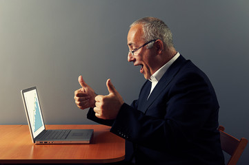 man looking at graph and showing thumbs up