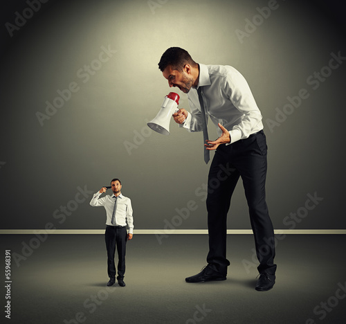 man screaming at small man with gun
