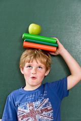 Junge mit Büchern und Apfel auf dem Kopf