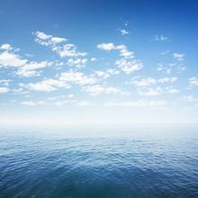 Błękitne niebo nad powierzchnią wody morza lub oceanu