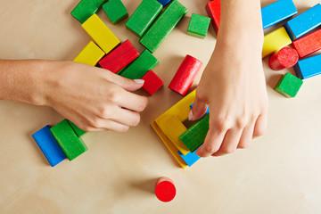 Hände spielen mit bunten Bausteinen
