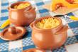 Two pots of millet porridge with sliced pumpkin