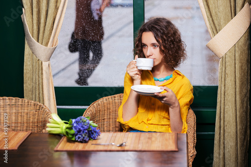 Sad young woman drinking tea at restaurant