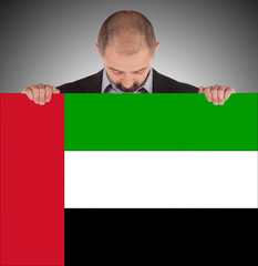 Businessman holding a big card, flag of the United Arab Emirates