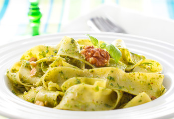 Tagliatelle pasta with pesto and walnuts on white plate