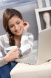 Attractive girl having tea by laptop