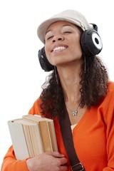 Ethnic girl enjoying music through earphones