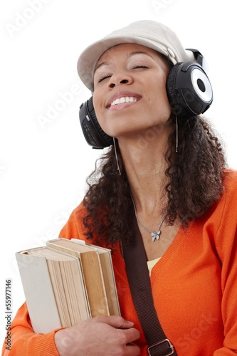 Ethnic girl enjoying music through earphones