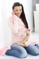 Smiling woman with soft toy and mobile