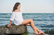 .Teenage girl in white shirt sitting on a rock in the sea