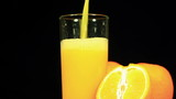 Orange juice is poured in a glass on a black background