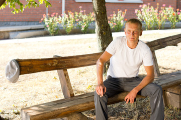Single man sitting lonely on a wooden bench