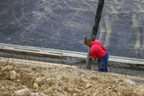 Worker pouring concrete on retaining wall 2
