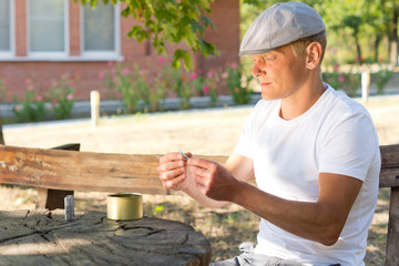 Caucasian man rolling a cigarette in a summer day
