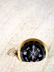 Old compass buried in sand