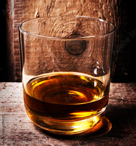 Glass of Scotch whiskey on old wooden background. An old and vin
