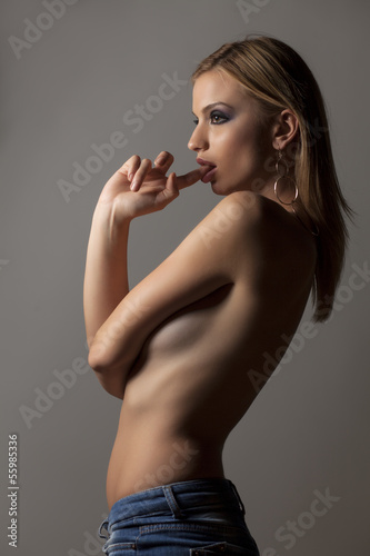 naked girl in a short jeans posing on gray background