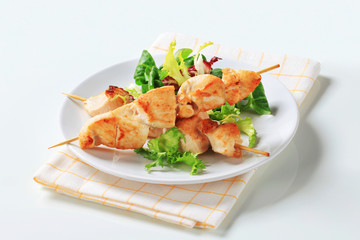 Chicken skewers and salad greens