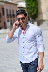 Handsome man in urban background talking on phone