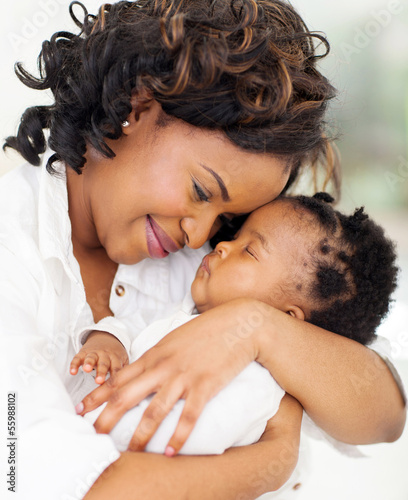 lvoing young african mother holding her asleep baby