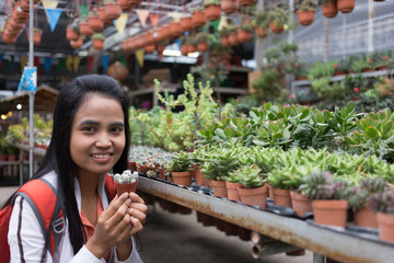 asian female hold cactus tree in garden nursery
