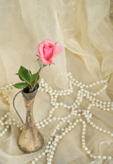 Pink rose in an antique silver vase with pearls