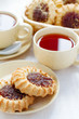 two cups of tea and biscuits with jam