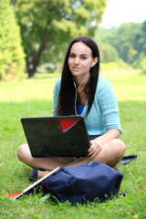 college student sitting on the grass working on laptop at campus