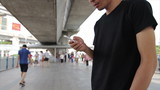 Asian male using smart in urban scene slow motion
