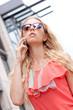 junge schöne blonde frau mit sonnenbrille und mobiltelefon