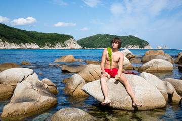 Young man is sitting on a rock