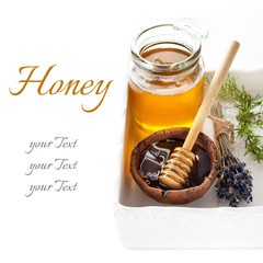 Glass jars of honey and a spoon of honey on white background