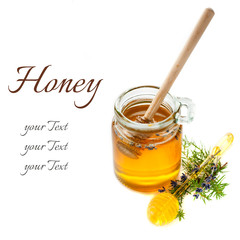 Glass jars of honey and a spoon of honey
