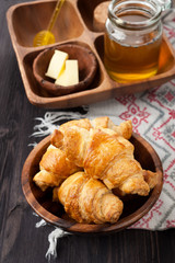 Croissants, honey and butter on a wooden background