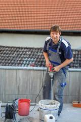 Young man tiling on balkony ceramic tiles
