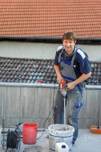 Young man tiling on balkony ceramic tiles