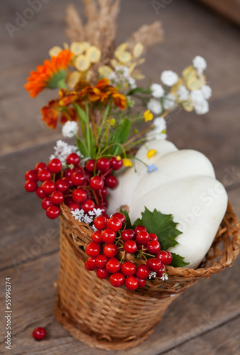 Autumn flowers, squash and berries in basket