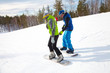 Young couple snowboarders in a ski resort