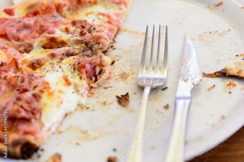Pizza leftovers in plate. Shallow depth of field.