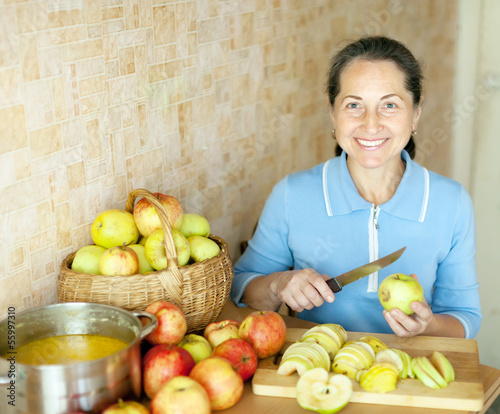 Woman cooks apple jam