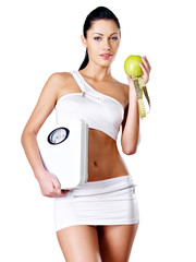 Healthy woman stands with the scales and green apple.