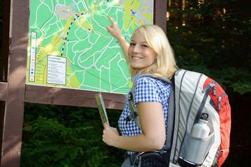 Wanderer steht vor Wegekarte
