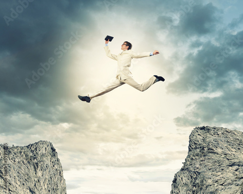 Businessman jumping over gap