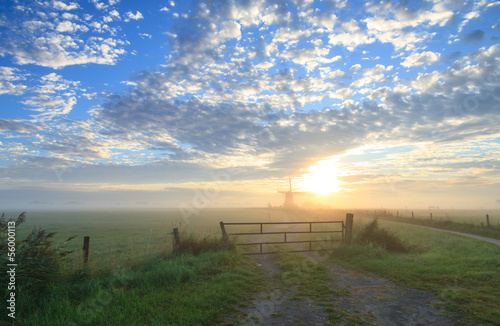 Foggy sunrise at a windmill.